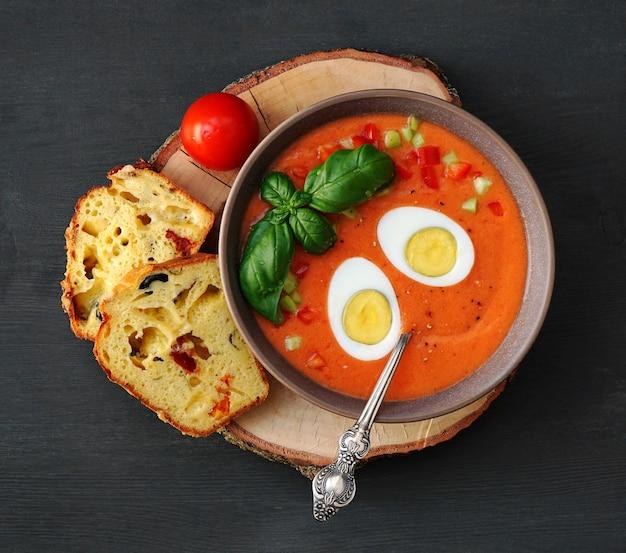 Tomatensoep gazpacho met ei en basilicum op een houten sneetje en sneetjes brood