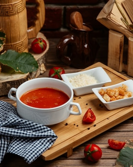 Tomatensoep geserveerd met broodvulling en geraspte parmezaanse kaas