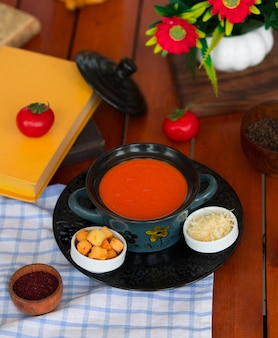Tomatensoep in een pot met gehakte parmezaanse kaas en broodcrackers.