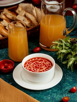 Tomatensoep in een witte kom en een glas sap
