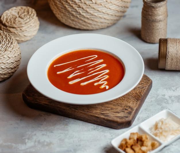 Tomatensoep in witte plaat met roomsaus erop.