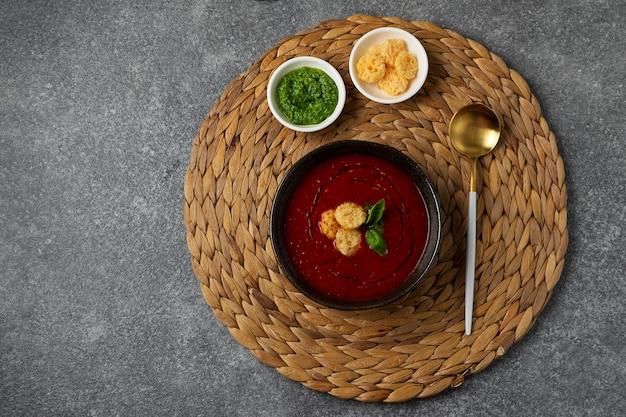 Tomatensoep in zwarte kom op grijze stenen tafel