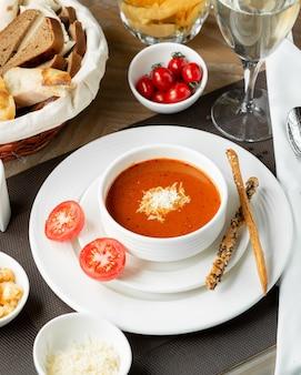 Tomatensoep met gehakte kaas en galetta-sticks.