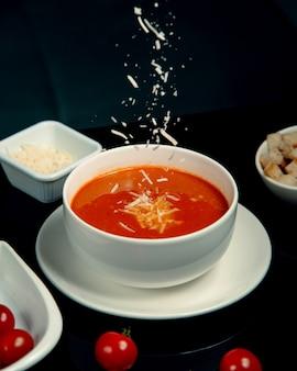 Tomatensoep met geraspte kaas en crackers