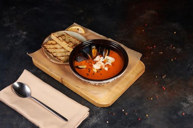 Tomatensoep met mosselen, inktvis, garnalen in kom. zeevruchten, donkere achtergrond