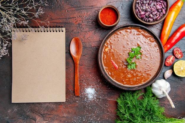 Tomatensoep verschillende kruiden knoflook citroengreens en notitieboekje op gemengde kleurentabel