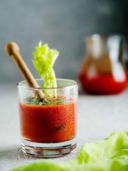 Tomatesap in glas met selderij.