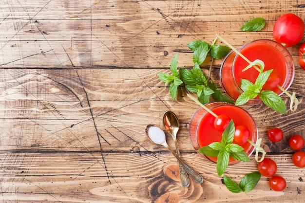 Tomatesap met munt in glas en verse tomaten op een houten tafel. gezond natuurvoedingconcept.