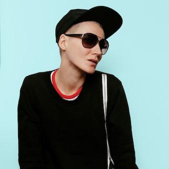 Tomboy stijlvolle fotomodel in een stedelijke outfit in zwarte kledingstijl
