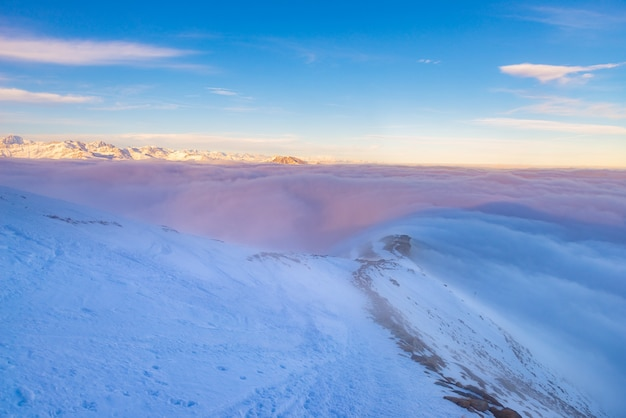 Toneel alpien landschap, wolken op de vallei arisign berg pieken zonsonderganglicht, de wintersneeuw.