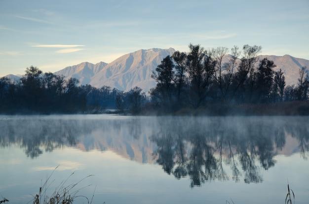 Toneelmeer met met weerspiegeling van bergen en bomen onder een blauwe hemel