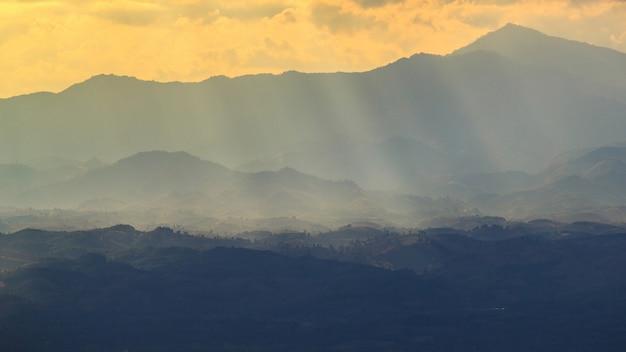 Toneelmening van de de winterbergen in zonsondergangtijd.