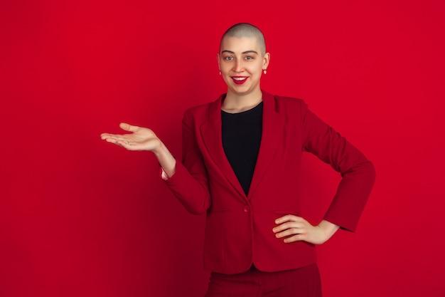 Tonen, presenteren. portret van jonge blanke kale vrouw geïsoleerd op rode muur.