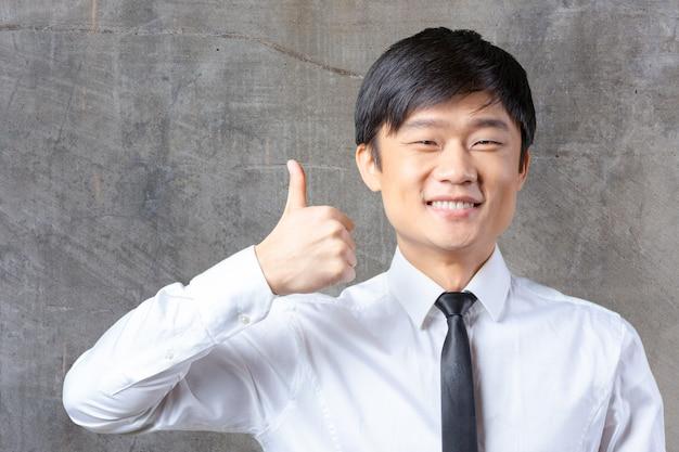 Tonend duim jonge aziatische bedrijfsmens