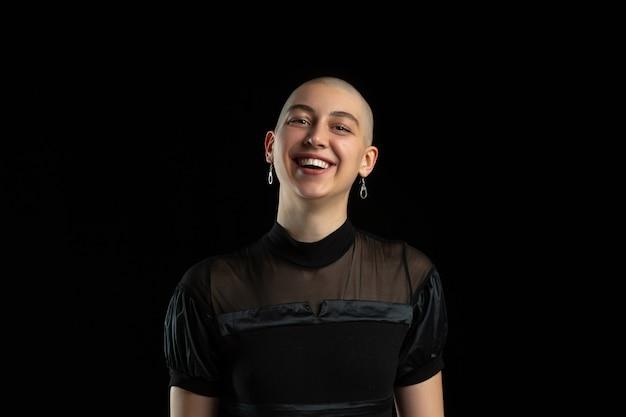 Tong uitgestoken, grimassen. zwart-wit portret van jonge blanke kale vrouw op zwarte muur. mooi vrouwelijk model. menselijke emoties, gezichtsuitdrukking, verkoop, advertentieconcept. jeugd cultuur.