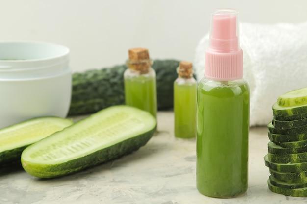 Tonic voor het gezicht met een komkommer. cosmeticaverzorging met komkommerextract op een lichte achtergrond. spa. schoonheid.