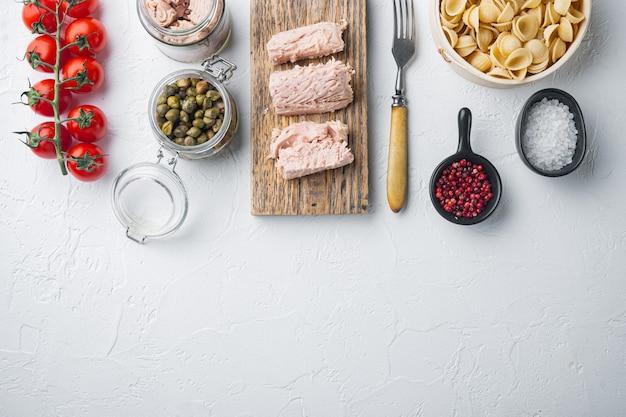 Tonijn pasta schelpen ingrediënten, op witte achtergrond, bovenaanzicht met kopie ruimte