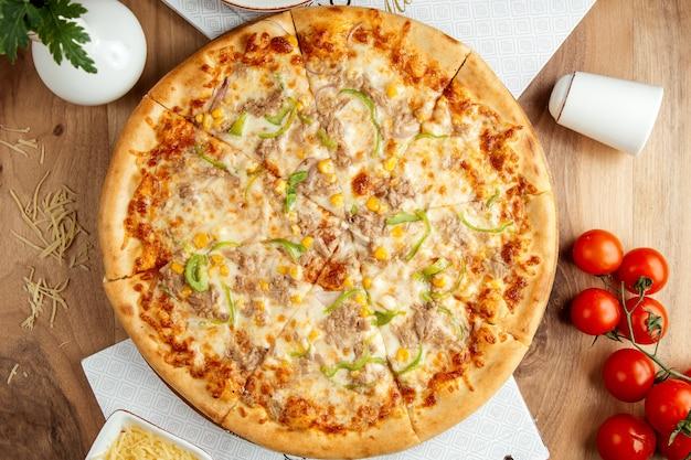 Tonijn pizza corns peper parmezaanse kaas bovenaanzicht
