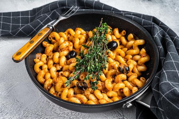 Tonijnpasta cellentani puttanesca in een pan.