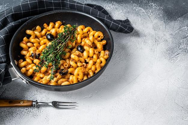 Tonijnpasta cellentani puttanesca in een pan