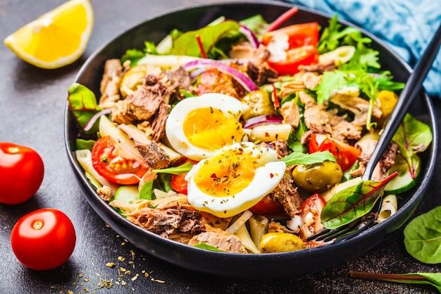 Tonijnsalade met deegwaren, olijven, groenten en ei in zwarte plaat