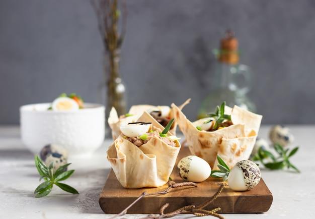 Tonijnsalade met komkommer, paprika, maïs en kwartel ei in taartjes gemaakt van lavash