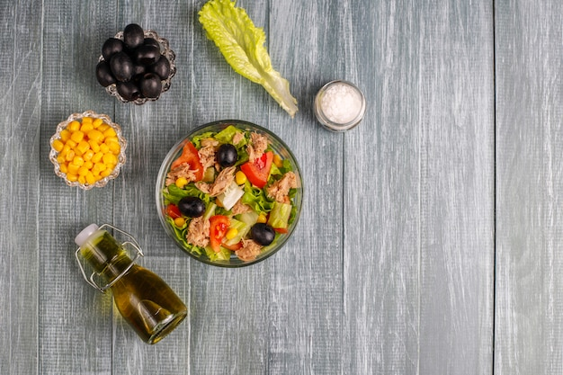 Tonijnsalade met sla, olijven, maïs, tomaten, bovenaanzicht
