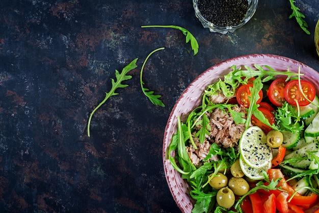 Tonijnsalade met tomaten, olijven, komkommer, paprika en rucola op rustieke achtergrond