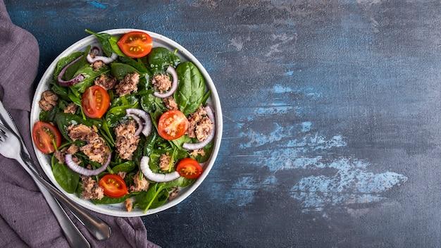 Tonijnsalade met tomaten, rode ui en spinazie. vissalade op een bord. bovenaanzicht, tekstruimte