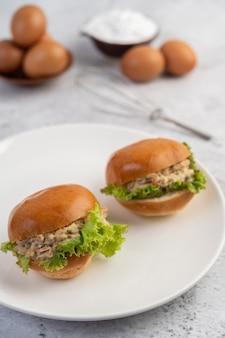 Tonijnsalade omwikkeld met brood en sla.