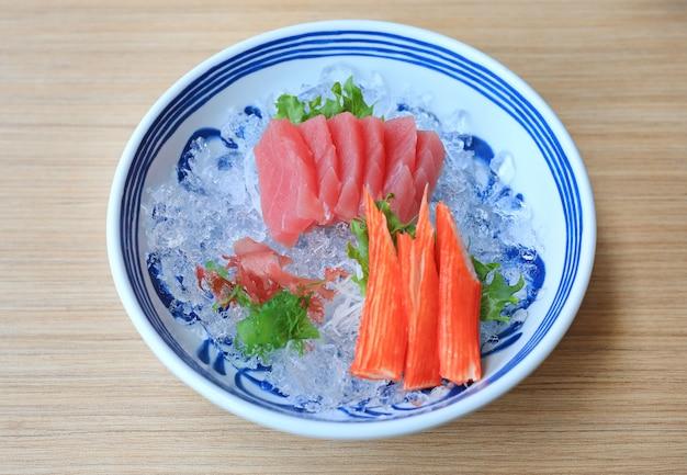 Tonijnsashimi geserveerd met zeewier en krabstokken op ijs.