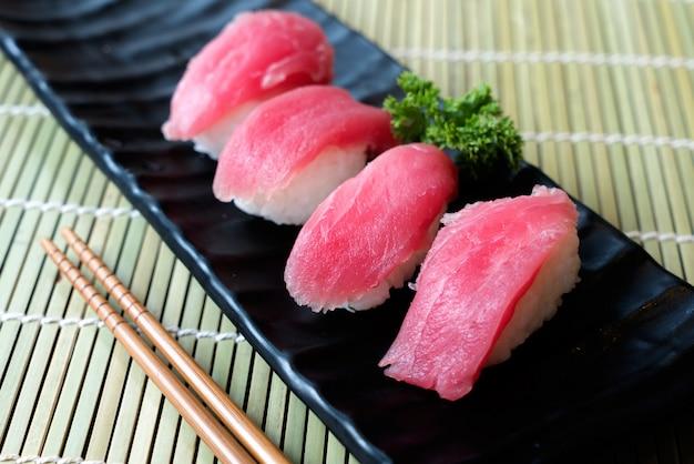 Tonijnsushi op zwarte plaat samen met japanse saus en groene bladdecoratie,