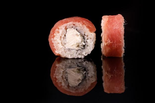 Tonijnsushi roll op een zwarte ondergrond met reflectie.