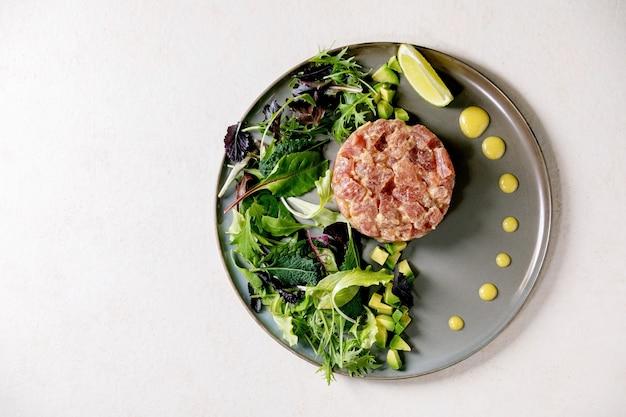 Tonijntartaar met groene salade, limoen, avocado en mosterdsaus die op ceramische plaat over witte textuurlijst dienen. plat leggen, kopie ruimte. fijn dineren, restaurantvoorgerecht