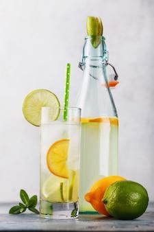 Tonische drank met citroen en limoen in een transparant glas met een open fles op tafel