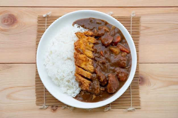 Tonkatsu, japanse gefrituurde varkensvleeskotelet bovenop met kerrie in witte schotel op houten lijst