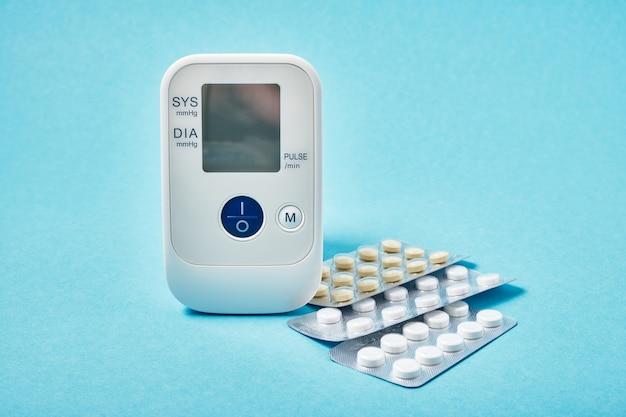 Tonometer hoge bloeddruk indicatie en pillen in folie blisters kopie ruimte bovenaanzicht