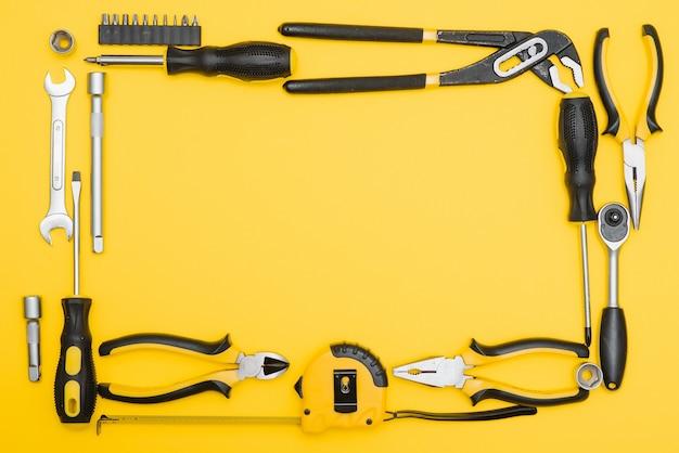Tools bovenaanzicht op gele achtergrond. tang, steeksleutels, schroevendraaiers en nietpistool plat met kopie ruimte.