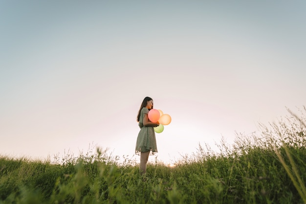 Toonfilm van eenzame aziatische vrouw die kleurrijke ballons op groen gebied met zonsondergangtijd houdt