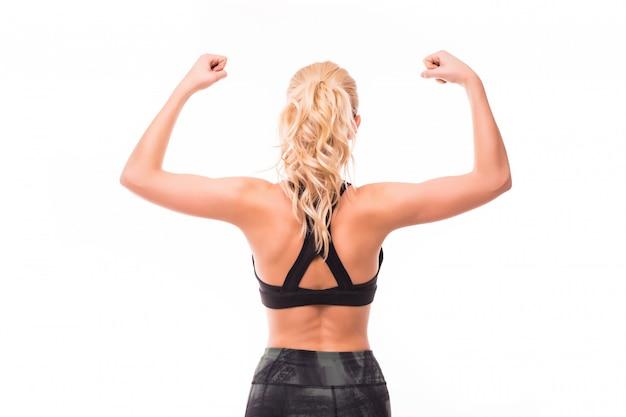 Toont de blonde jonge dame in zwarte bovenkant haar spieren van rug op wit wordt geïsoleerd dat