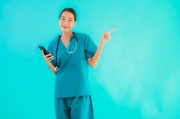 Toont de portret mooie jonge aziatische artsenvrouw slimme mobiele telefoon