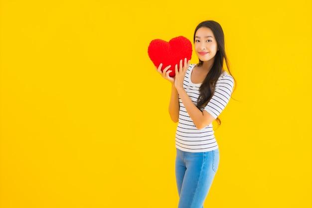 Toont de portret mooie jonge aziatische vrouw harthoofdkussen