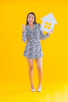 Toont de portret mooie jonge aziatische vrouw huis of huisteken op geel