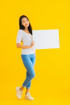 Toont de portret mooie jonge aziatische vrouw leeg wit aanplakbordteken