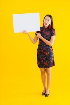 Toont de portret mooie jonge aziatische vrouwenslijtage chinese kleding wit leeg aanplakbord