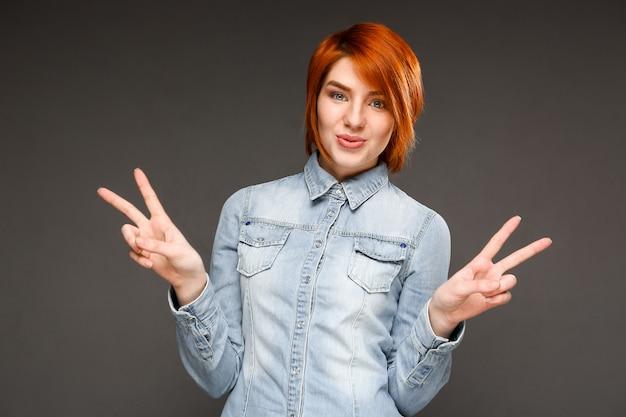 Toont de roodharige leuke vrouw vredesteken