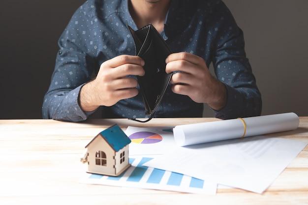 Toont een lege portemonnee voor een huisproject en een huis