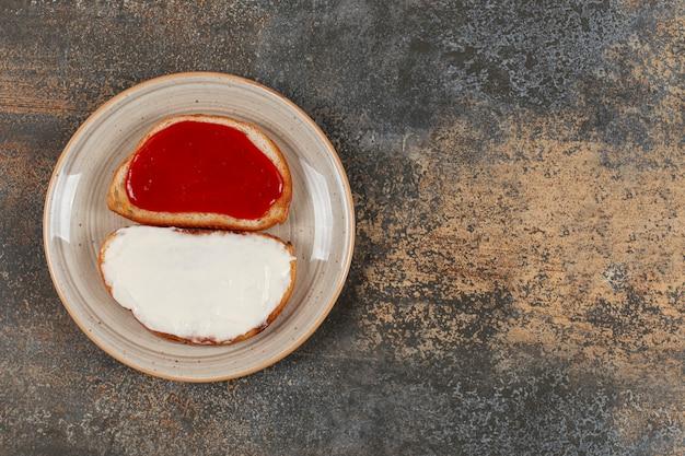 Toosts met aardbeienjam en zure room op ceramische plaat.