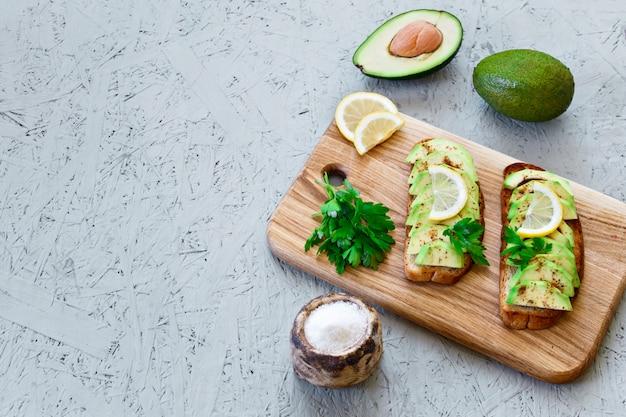 Toosts met avocado, citroen, spaanse peper of paprika op een grijze achtergrond