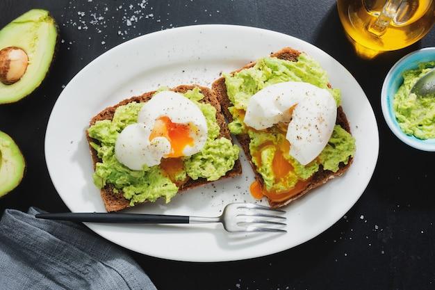 Toosts met avocado en eieren die op plaat worden gediend. detailopname.